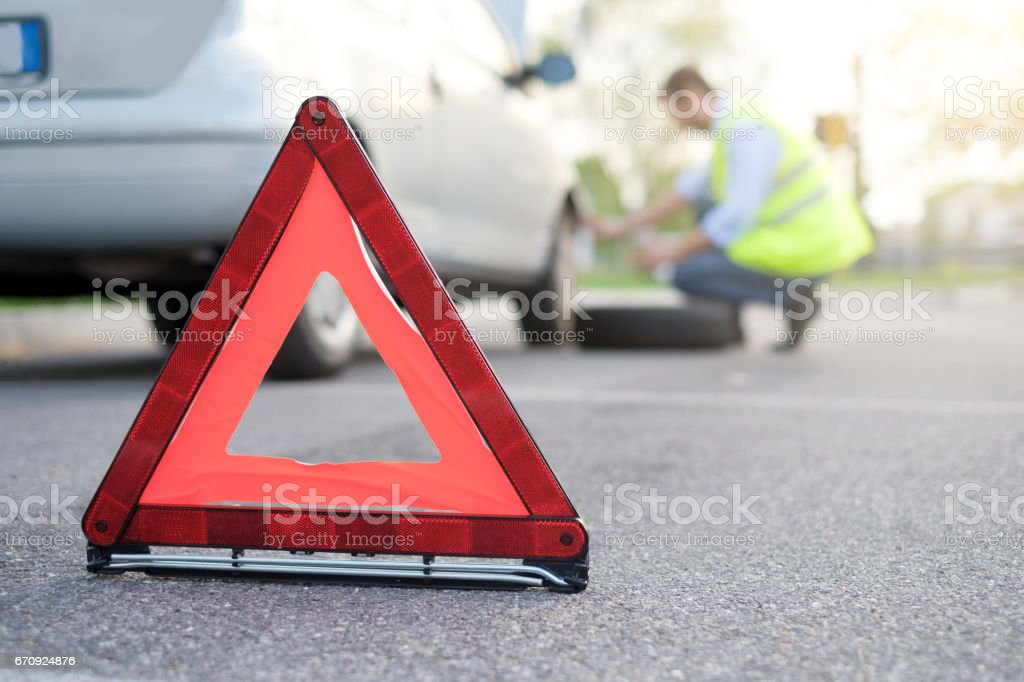Man changing one flat tyre after vehicle breakdown stock photo