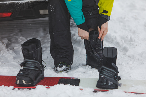 man changing regular boots to snowboard at parking place near car