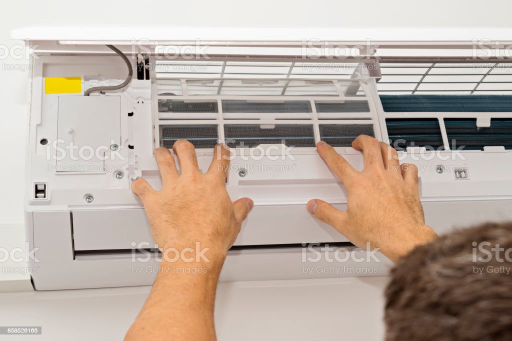 Man Changing the Filter in the Air Conditioning stock photo