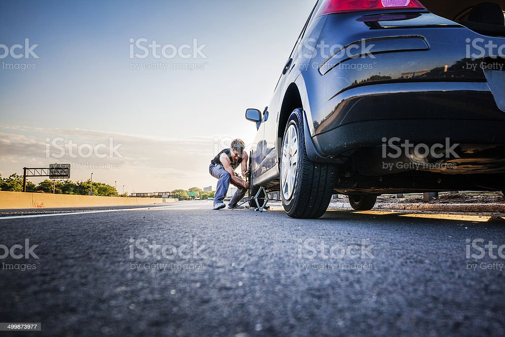 Man changing the flattened tyre at the highway stock photo