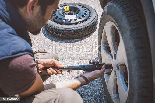 104275470istockphoto Man Changing Wheel On Roadside 841036664