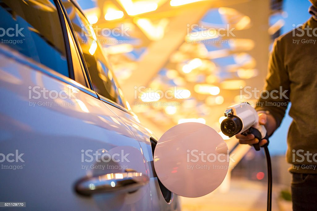 Man charging electric car stock photo