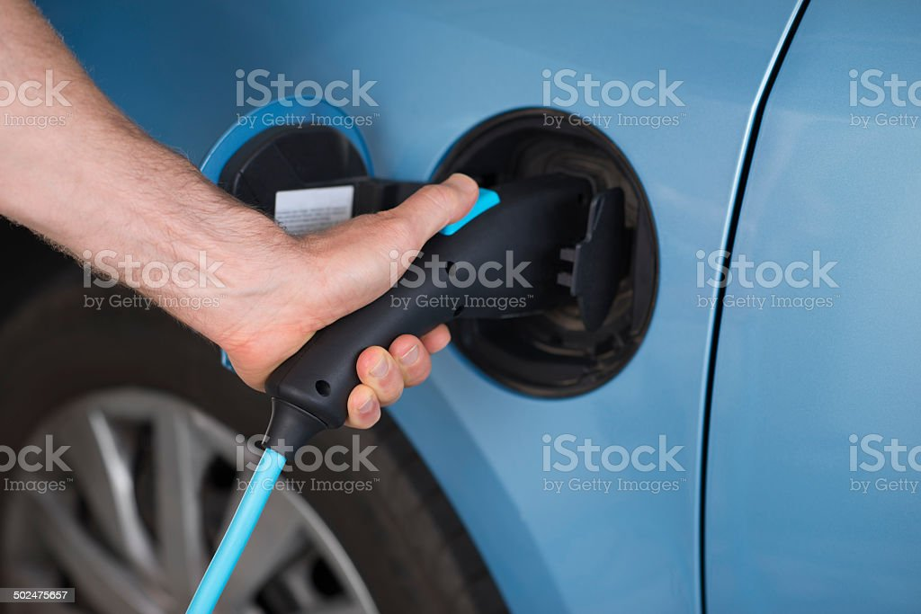 Man charging of an electric blue car. stock photo