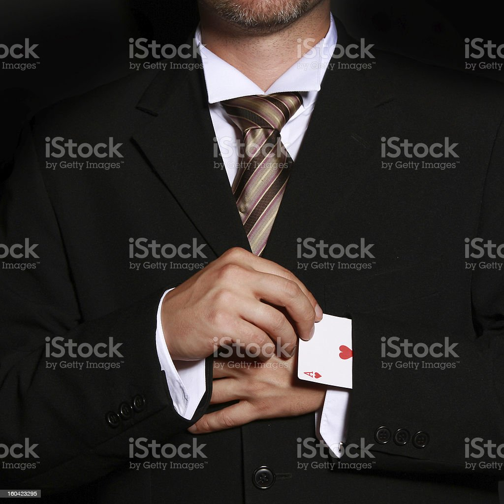 man cheating with playing cards stock photo