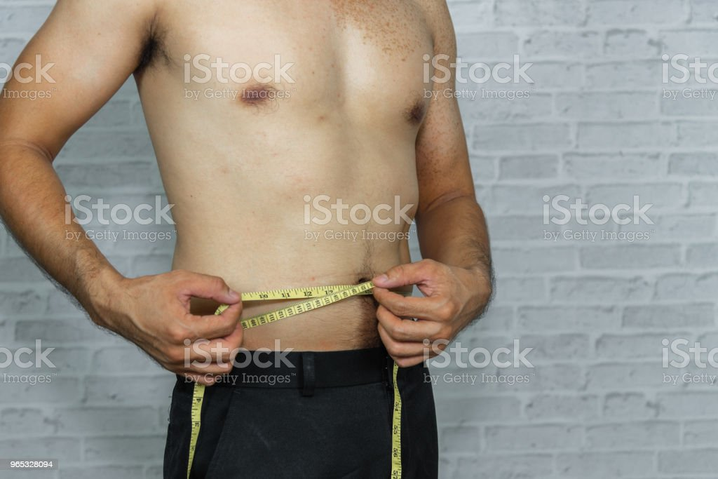 man check out his body fat with measuring tape royalty-free stock photo