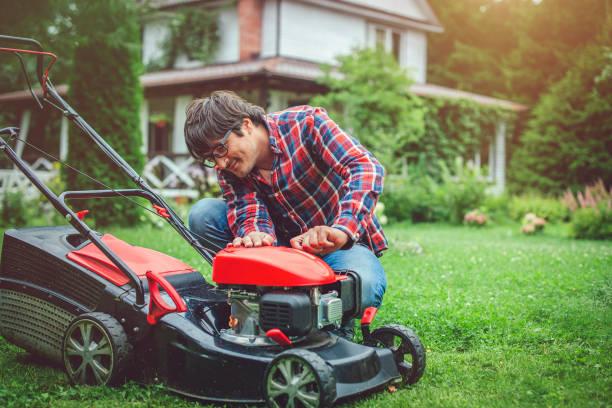 Mann prüft Rasenmäher in seinem Hinterhof – Foto