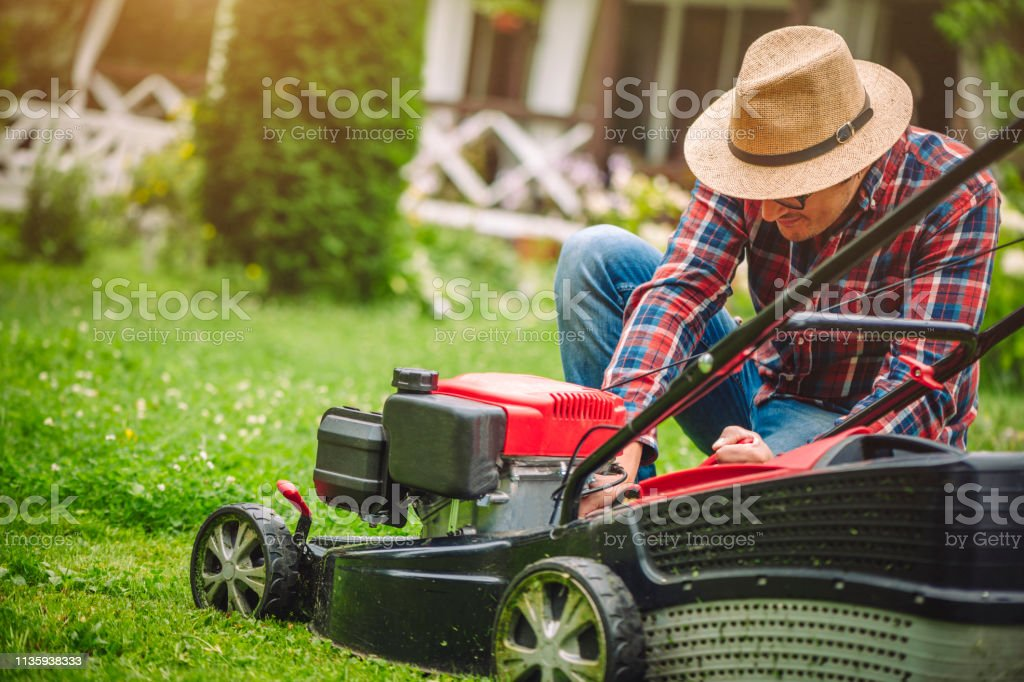 Man is about to mow grass near his house