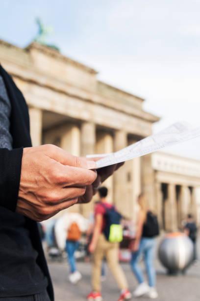Mann prüft eine Karte am Brandenburger Tor, Berlin – Foto