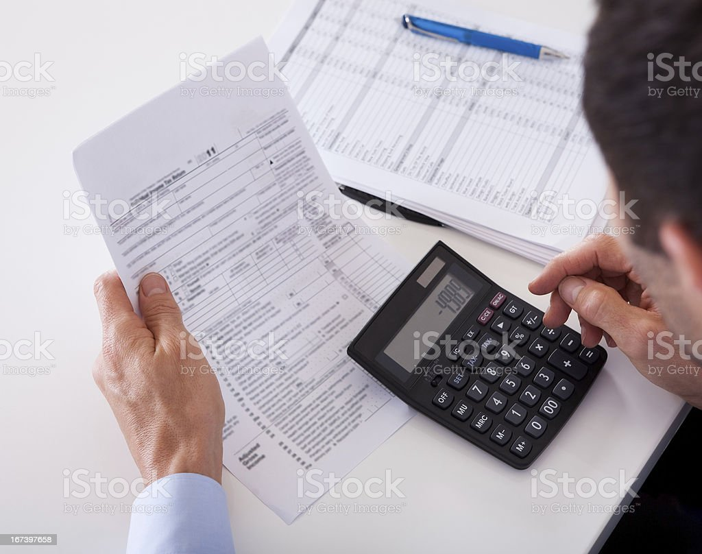 Man checking an invoice on a calculator stock photo