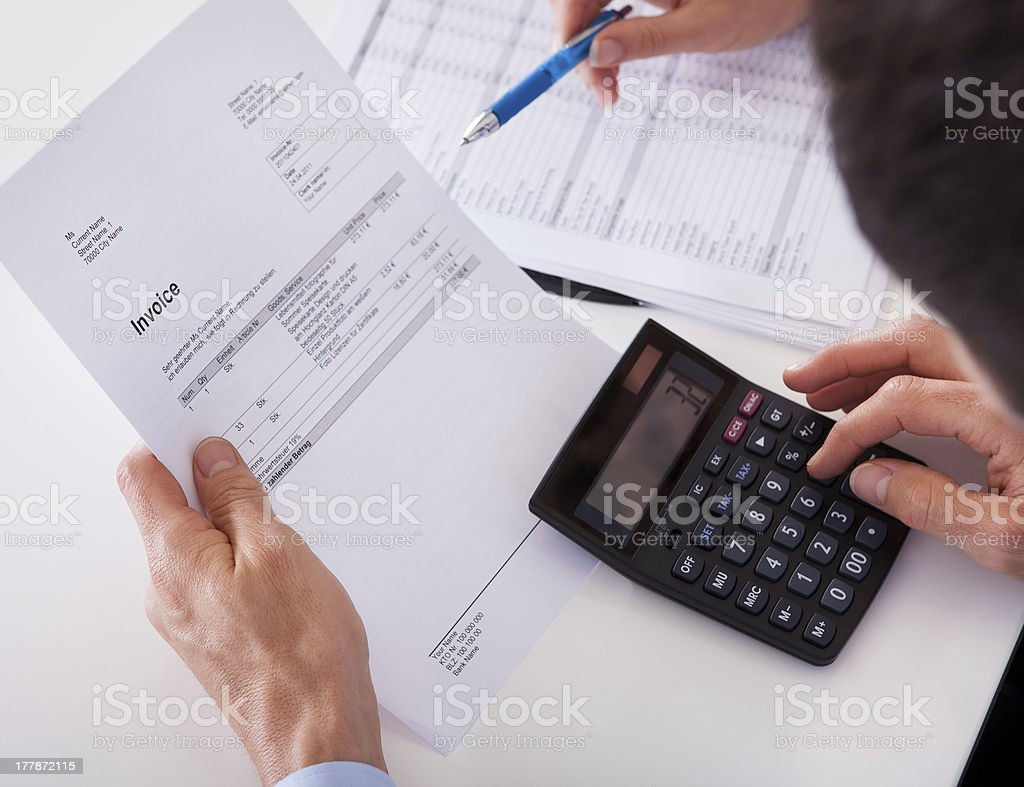 Man checking an invoice on a calculator royalty-free stock photo