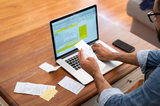 man checking bills at home - scontrino foto e immagini stock