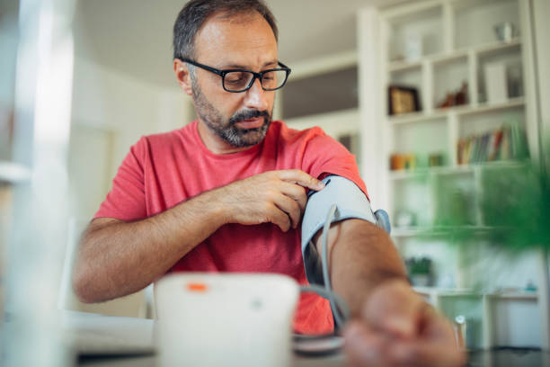 Man checking blood presure Photo of man preparatio checking blood presure at home hypertensive stock pictures, royalty-free photos & images