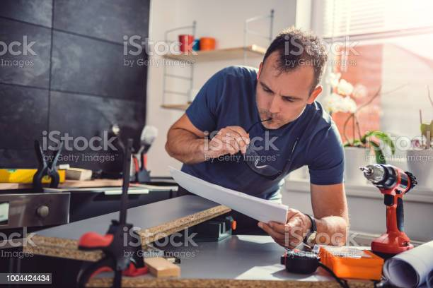 Man checking blueprints while building kitchen cabinets picture id1004424434?b=1&k=6&m=1004424434&s=612x612&h=ojmw3ej5p9h90gxfz3swxogt4rxzyzlqx6oqgo zkws=