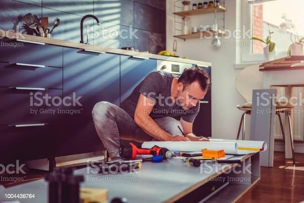 Man checking blueprints while building kitchen cabinets picture id1004436764?b=1&k=6&m=1004436764&s=612x612&h=zqrla8yd ixuilslzpvyxwv 8vqqnnpbxhyjyg5syxu=