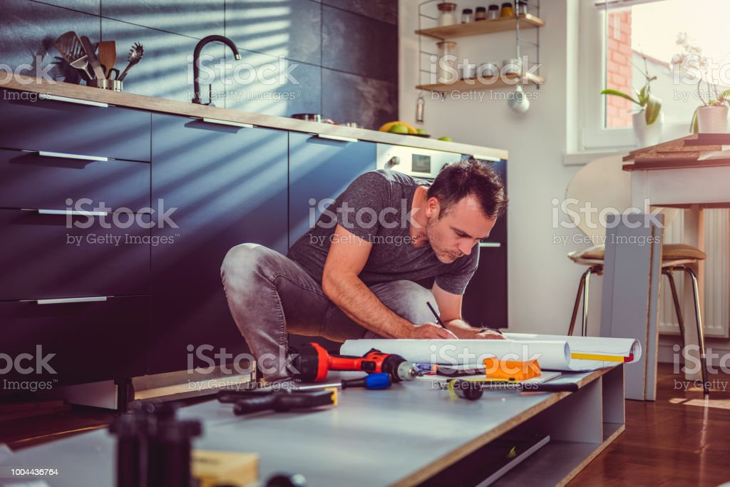 Man checking blueprints while building kitchen cabinets stock photo