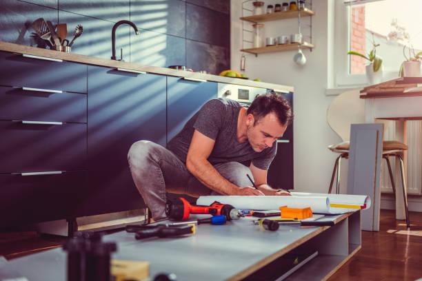 man kontrollera ritningar samtidigt bygga köksskåp - husutbyggnad bildbanksfoton och bilder