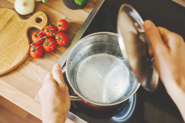 끓는 물 냄비 요리를 확인 하는 남자. - 뚜껑 뉴스 사진 이미지