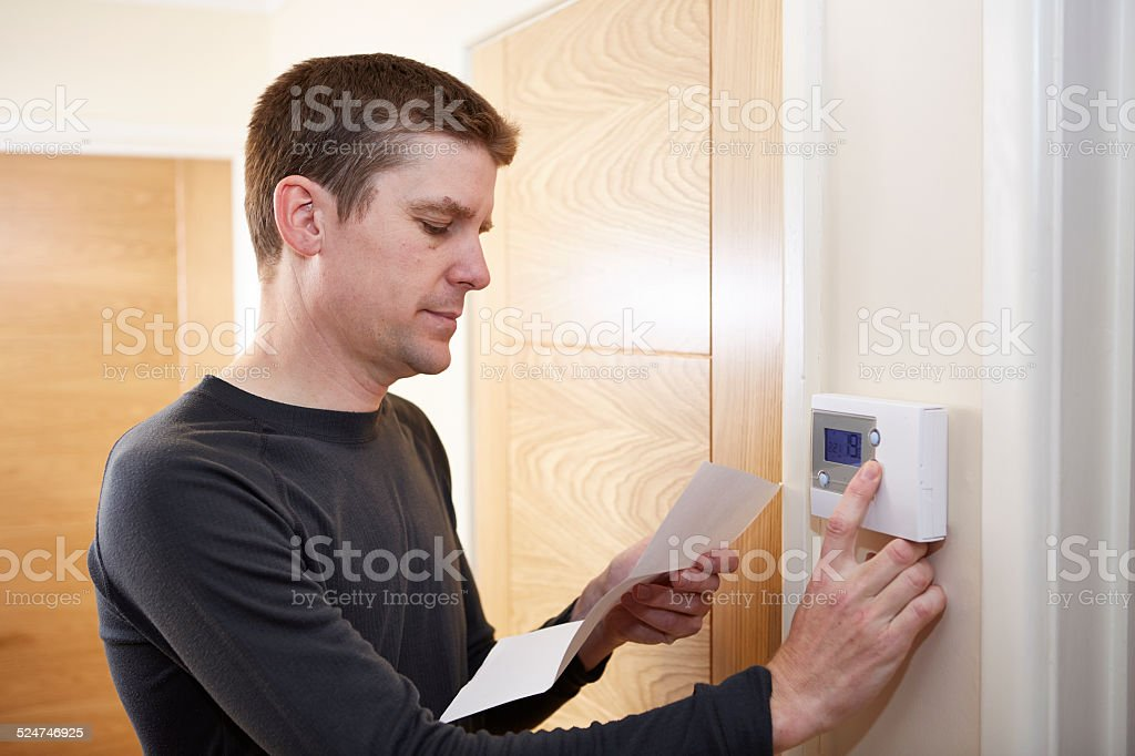 Man checking energy bill and adjusting digital thermostat stock photo