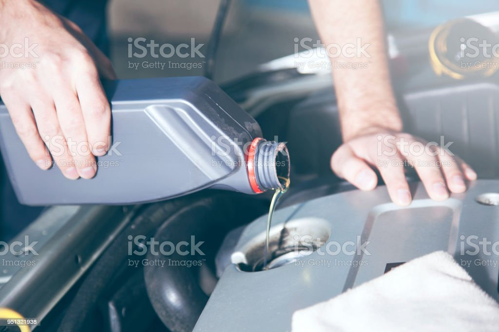 Man checking engine oil of an  car stock photo