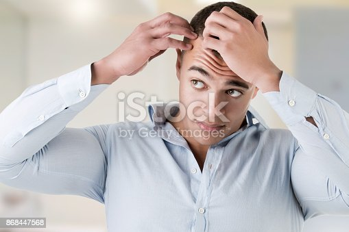istock Man checking hairline, in a bathroom 868447568