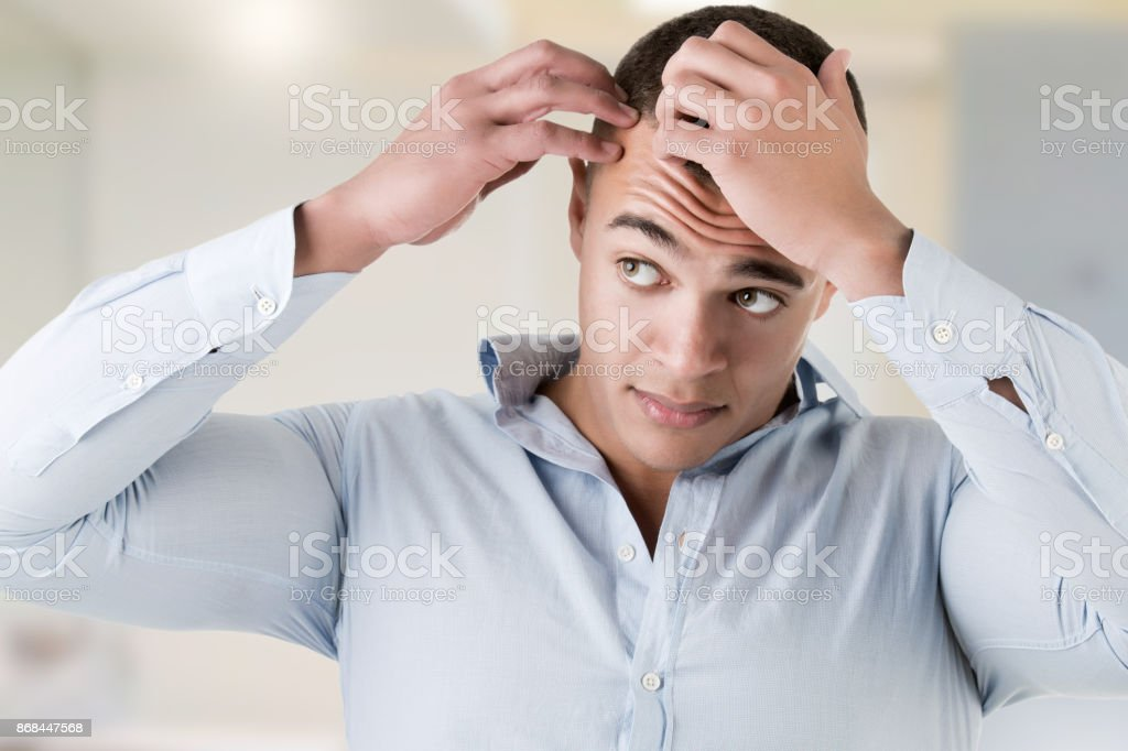 Man checking hairline, in a bathroom stock photo