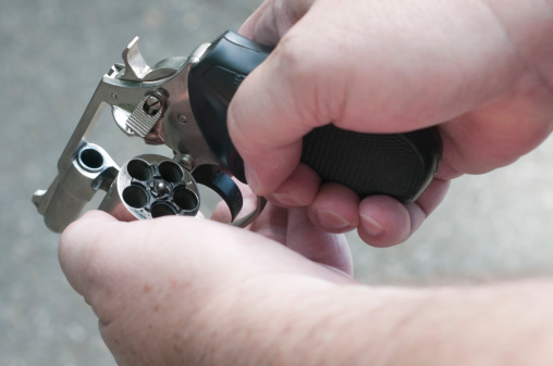 Man Checking Handguns Cylinder Stock Photo - Download Image Now