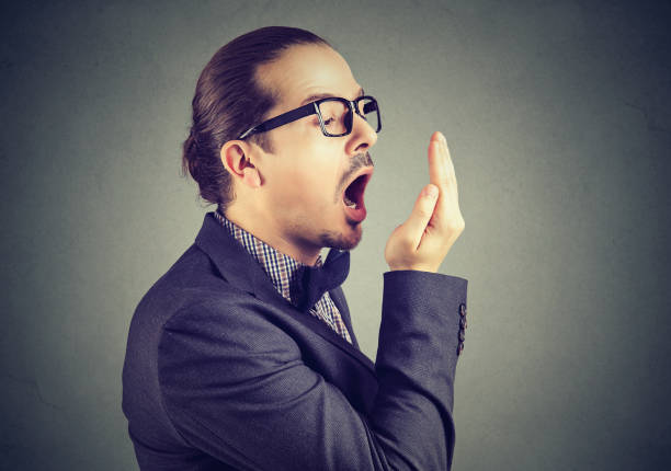 man checking his breath with hand test gesture. stock photo