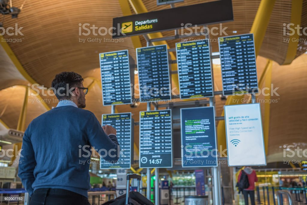 man checking his flight on the timetable display at the airport stock photo