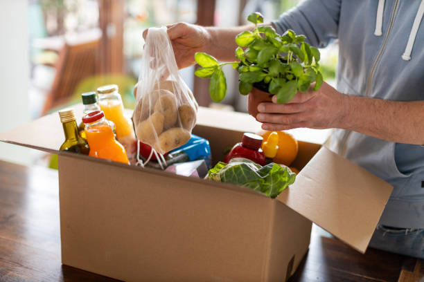 man checking his fresh food delivery - grocery home foto e immagini stock