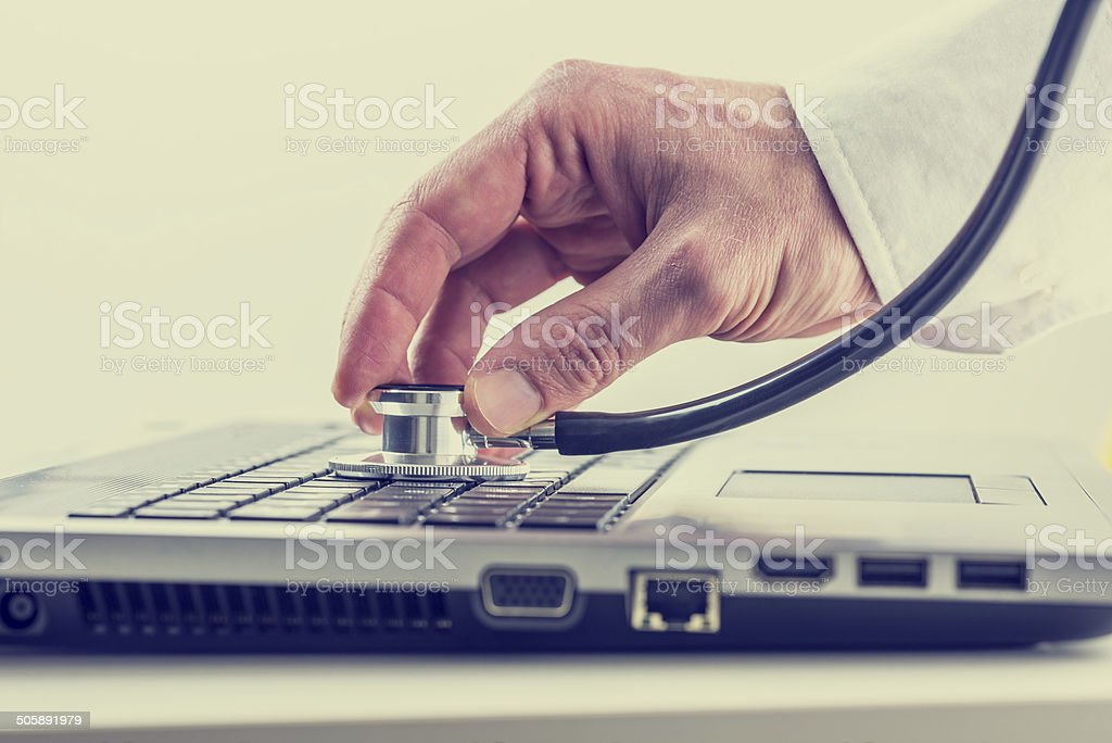Man checking his laptop with a stethoscope stock photo
