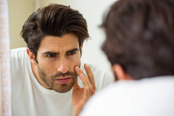 Man checking his skin in bathroom Man looking in mirror and checking his skin in bathroom hair stubble stock pictures, royalty-free photos & images