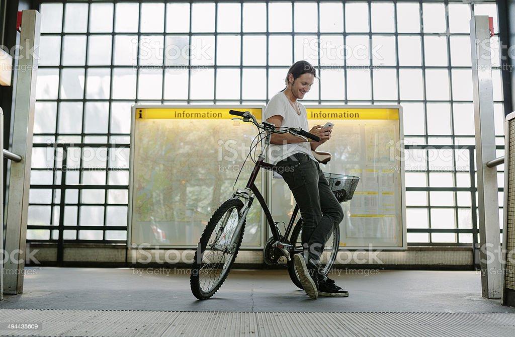 Man checking his smartphone at subway station stock photo