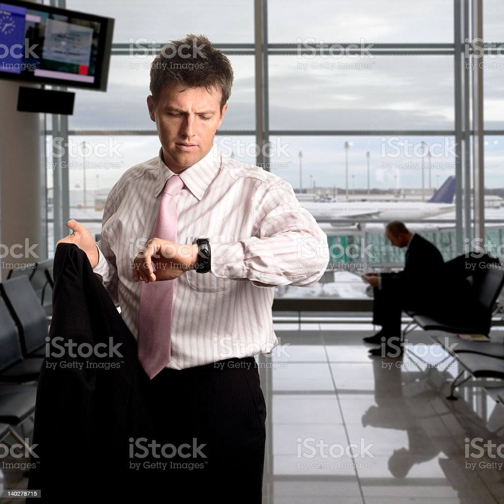 A man checking his watch, waiting for a flight royalty-free stock photo