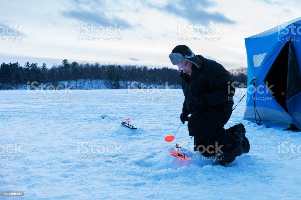 Man checking ice fishing hole stock photo