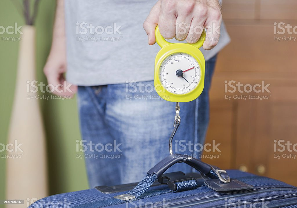 Man checking luggage weight with steelyard balance stock photo