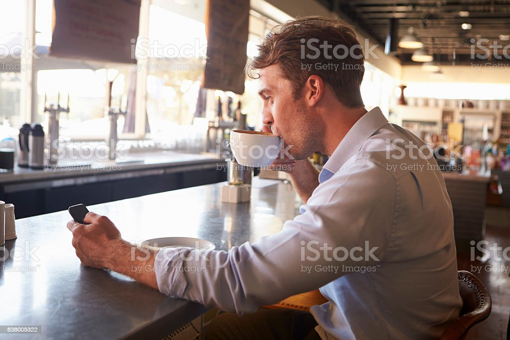 Man Checking Messages On Phone In Coffee Shop stock photo