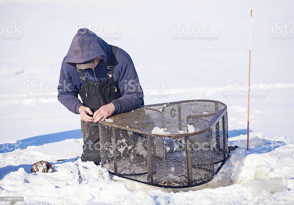 Man Checking Minnow Trap in Winter stock photo