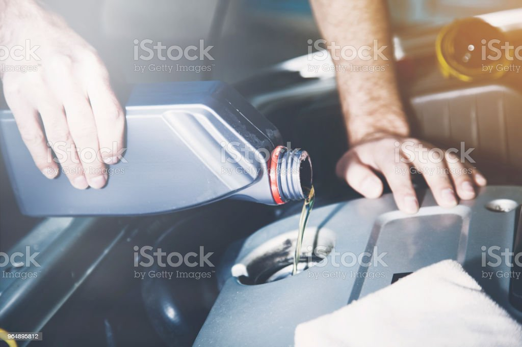 Man checking  oil of an older car royalty-free stock photo