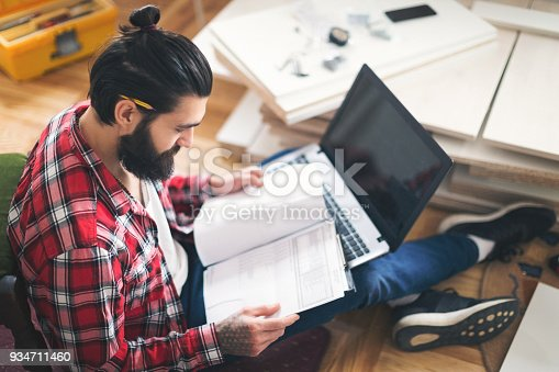 452592895 istock photo Man checking plans for new furniture 934711460