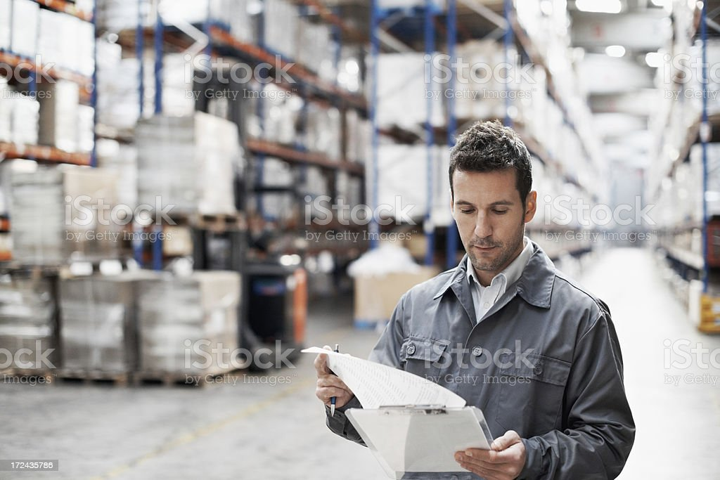 Man checking stock in a warehouse stock photo
