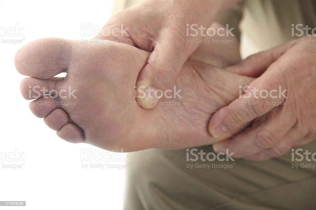 man checks his aching foot stock photo