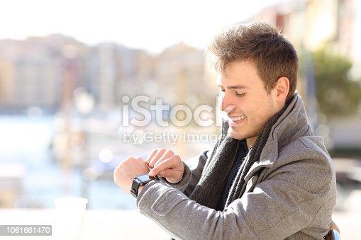 Happy man checks smartwatch in a coffee shop in winter