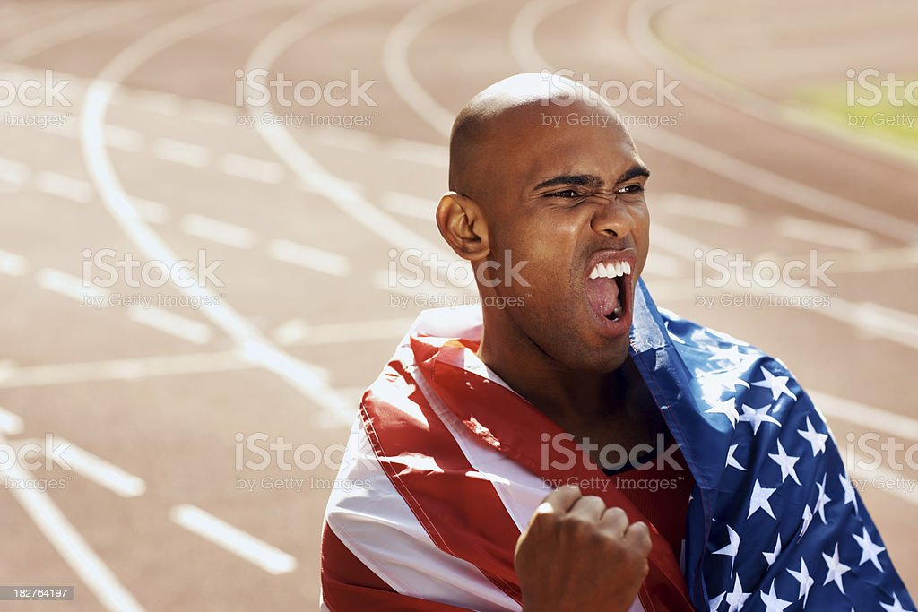 Man cheering with American flag around his shoulders royalty-free stock photo