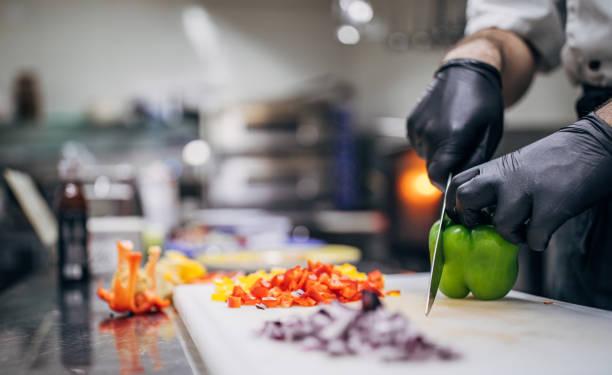 Man chef cutting vegetables in kitchen