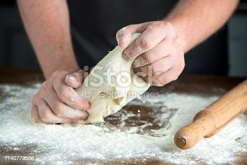 Man chef  preparing bread dough on wooden table.