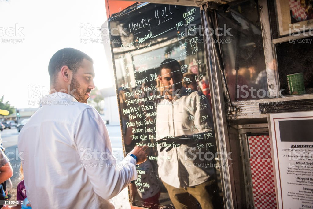 Man Chooses a Meal from Menu Posted on Food Truck stock photo