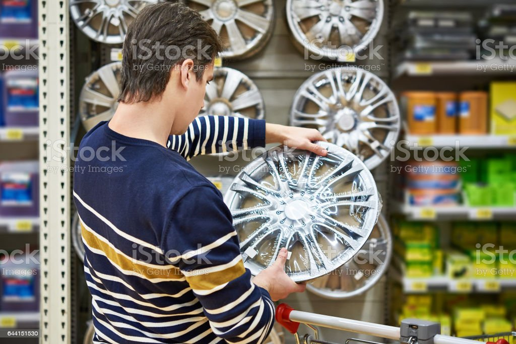 Man chooses alloy wheels for your car wheels in supermarket stock photo