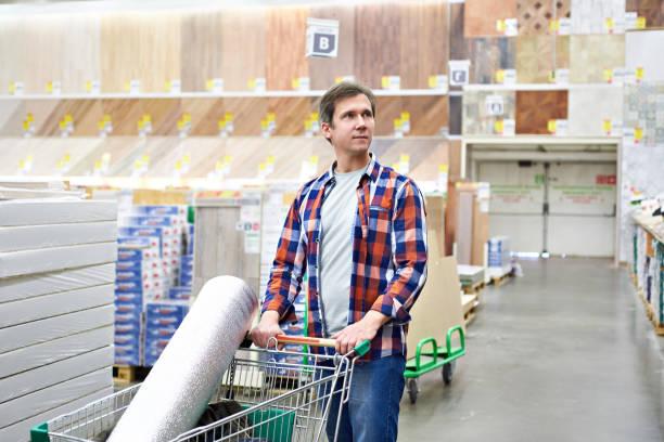 man chooses and buys goods in store - material de construção imagens e fotografias de stock