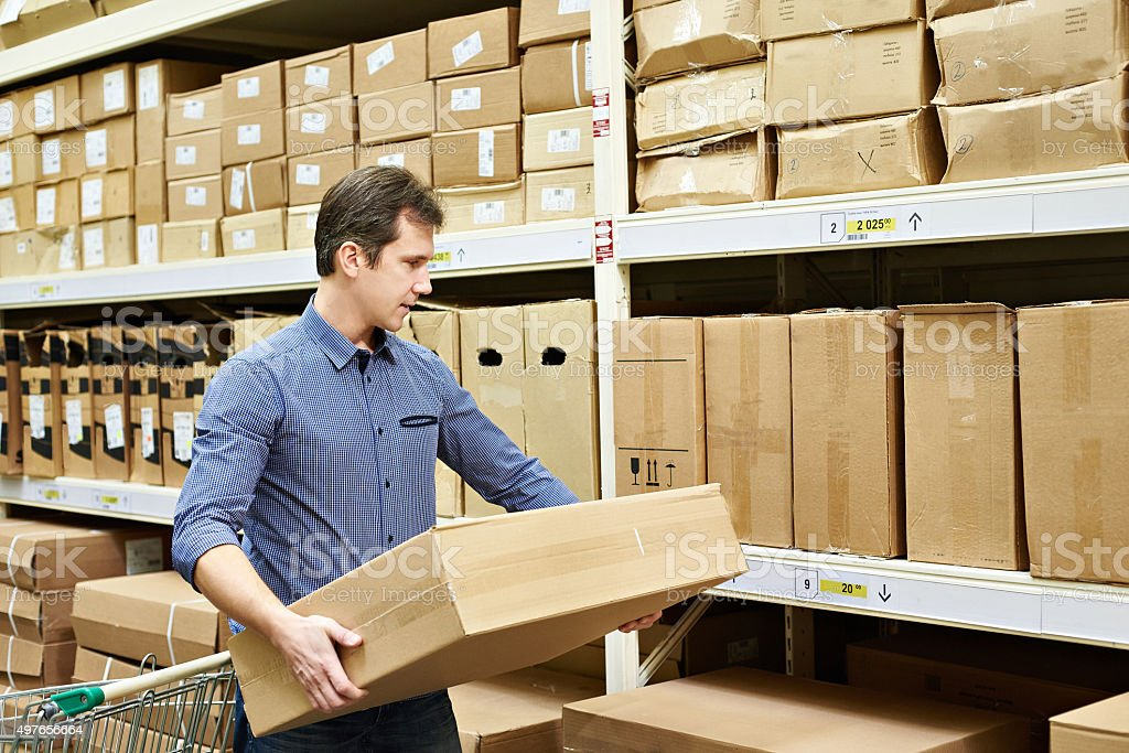 Man chooses box of goods in stores stock photo