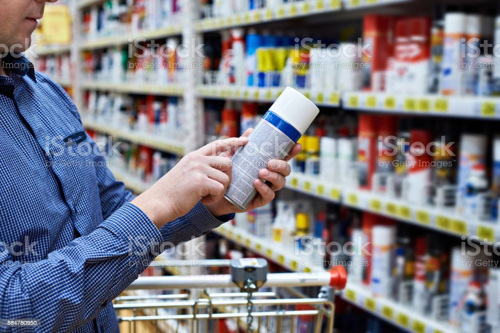 Man chooses chemical products for car in store stock photo